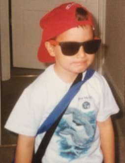 young boy in red baseball cap and dark sunglasses